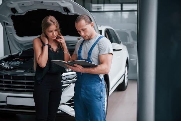 Nieuwe apparatuur nodig. resultaten van reparatie. zelfverzekerde man die laat zien wat voor schade haar auto is aangericht