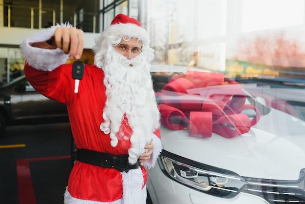 Nieuwe auto als kerstcadeau. santa claus in de autoshowroom dichtbij een nieuwe auto.