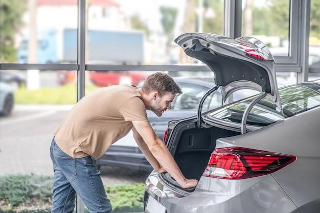Nieuwe auto. ernstige jonge volwassen man in vrijetijdskleding op zoek naar open kofferbak van auto leunend met handen in dealerschap