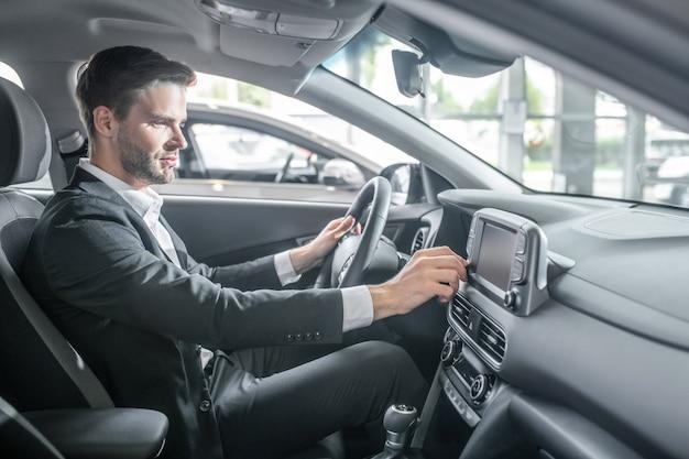 Nieuwe auto. glimlachende geïnteresseerde jongeman in pak zit aan het stuur van de auto en raakt het dashboard aan met zijn hand