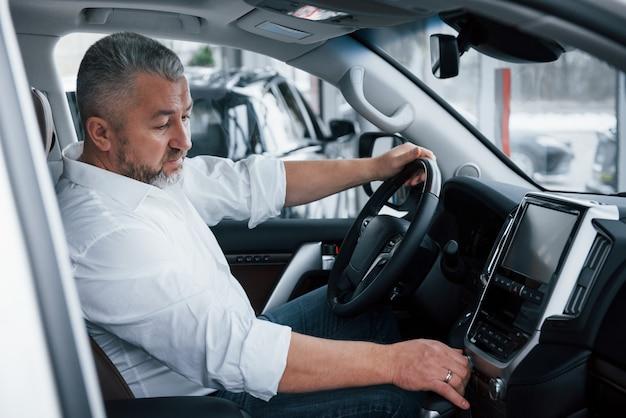 Nieuwe auto kopen en testen. senior zakenman in officiële kleding zit in een luxeauto en het indrukken van de knoppen op de muziekspeler