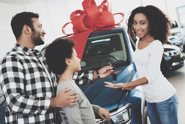 Nieuwe auto met rode boog man geeft sleutels tot vrouw