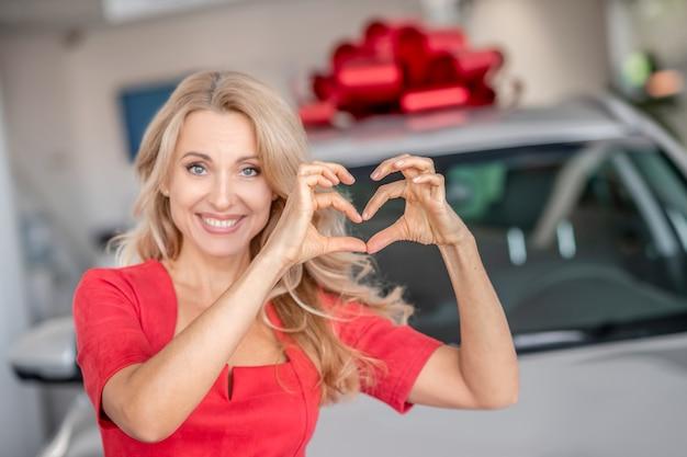 Nieuwe auto. mooie vrouw in een rode jurk op zoek opgewonden staande in de buurt van de nieuwe auto