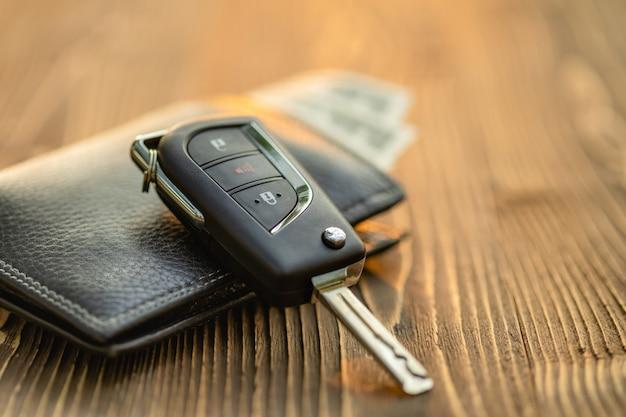 Nieuwe autosleutels met amerikaanse dollarbankbiljet op houten lijst. auto aankoop of autoverhuur concept