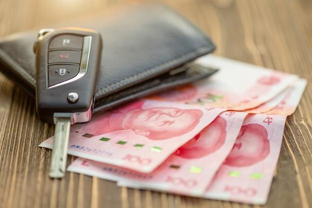 Nieuwe autosleutels met chinees bankbiljet op houten lijst. auto aankoop of autoverhuur concept