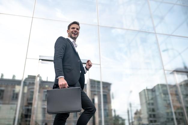 Nieuwe baan. jonge zakenman gaat naar het kantoor werken en een goed gevoel