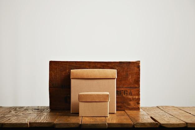 Nieuwe beige kartonnen dozen stonden in contrast met een vintage wijnkrat en een bruine rustieke tafel die op wit wordt geïsoleerd