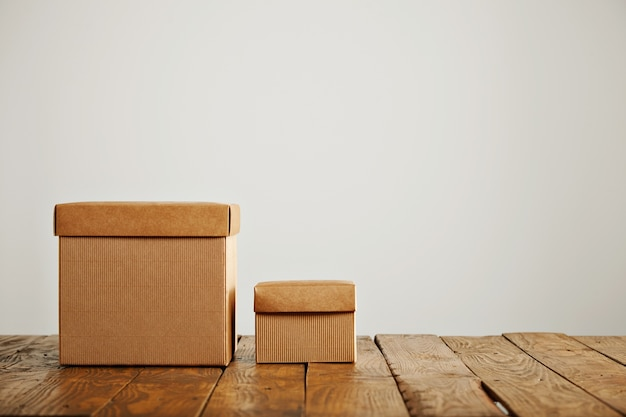 Nieuwe beige kartonnen dozen van verschillende afmetingen met deksels in contrast met een oude ruwe houten tafel in een studio met witte muren