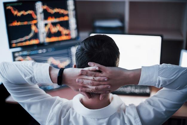 Nieuwe benaderingen ontwikkelen. achteraanzicht van de jonge man in vrijetijdskleding die hand op de achterkant van het hoofd houdt en werkt terwijl hij aan het bureau in creatief kantoor zit.