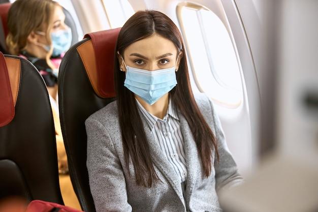 Nieuwe bestelling in vliegtuig. vrouw zit in masker voor vliegen