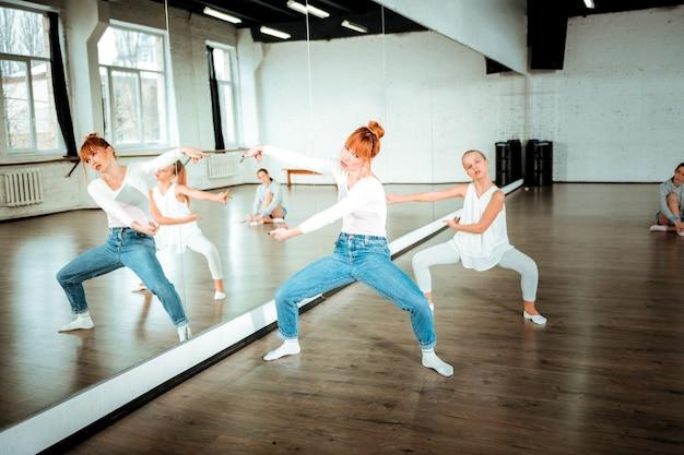 Nieuwe bewegingen. roodharige balletleraar en haar student kijken druk terwijl ze nieuwe bewegingen leren