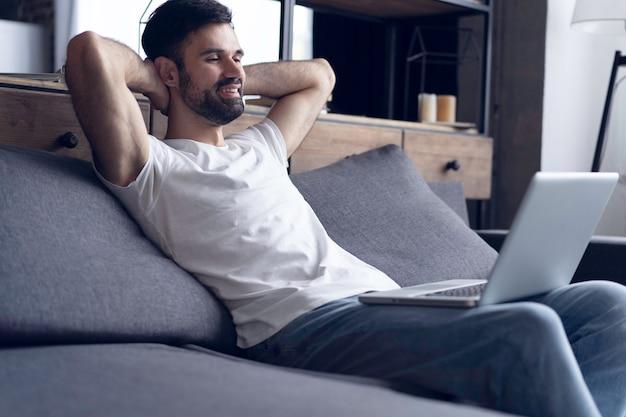 Nieuwe blogpost typen. zijaanzicht van de knappe jonge man met behulp van zijn laptop met een glimlach terwijl hij thuis op de bank zit.