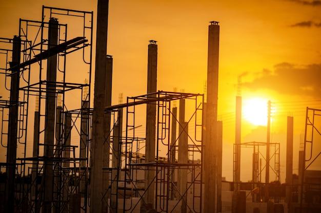 Nieuwe bouwplaats met stalen framestructuur bij zonsondergang of zonsopgang hemelachtergrond.
