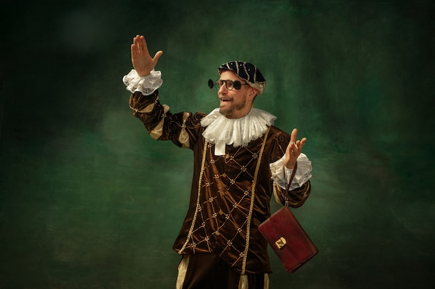 Nieuwe brillen proberen. portret van middeleeuwse jonge man in vintage kleding met houten frame op donkere achtergrond. mannelijk model als hertog, prins, koninklijk persoon. concept vergelijking van moderne tijdperken, mode.