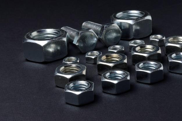 Nieuwe chromen moeren en bouten van verschillende groottes liggen tegen een donkere tafel. detailopname.