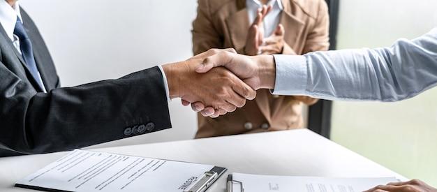 Nieuwe collega's begroeten, handdruk tijdens sollicitatiegesprekken, mannelijke kandidaat handen schudden met interviewer of werkgever na een sollicitatiegesprek, werkgelegenheid en wervingsconcept.