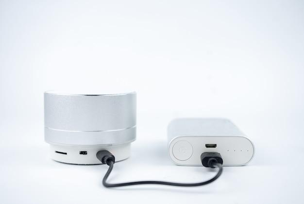 Nieuwe draadloze grijze miniluidsprekers zonder naam opladen met powerbank op witte achtergrond