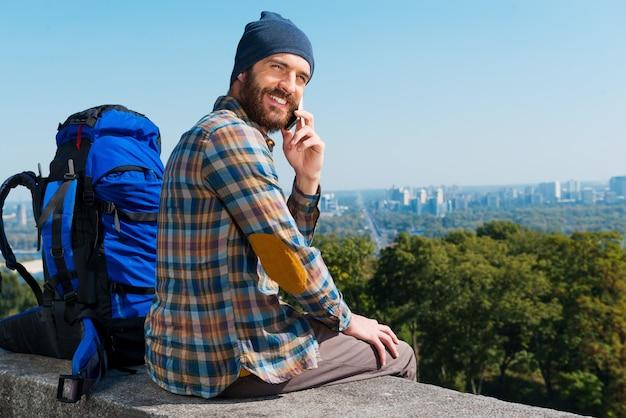 Nieuwe emoties delen. knappe jonge man die in de buurt van een rugzak zit en met een glimlach door de schouders naar de camera kijkt terwijl hij aan de telefoon spreekt