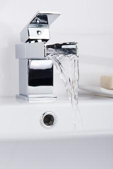 Nieuwe en moderne stalen kraan met de keramische wasbak in de badkamer