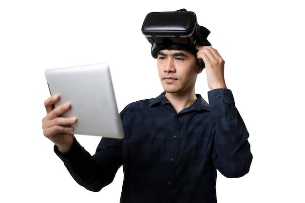 Nieuwe ervaring. man gebruiken moderne technologie. werken op tablet en vr-bril voor virtual reality.