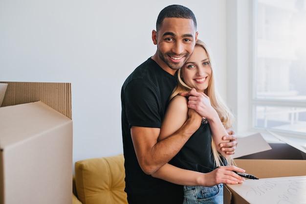 Nieuwe familie gaat verhuizen in een nieuw appartement, vrolijk paar inpakken voor verhuizing. jonge man en vrouw knuffelen, ze rond dozen in lege ruimte. vrijetijdskleding dragen.