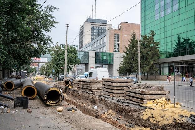 Nieuwe geïsoleerde zwarte waterleidingen en betonplaten op stadsweg in zomerdag