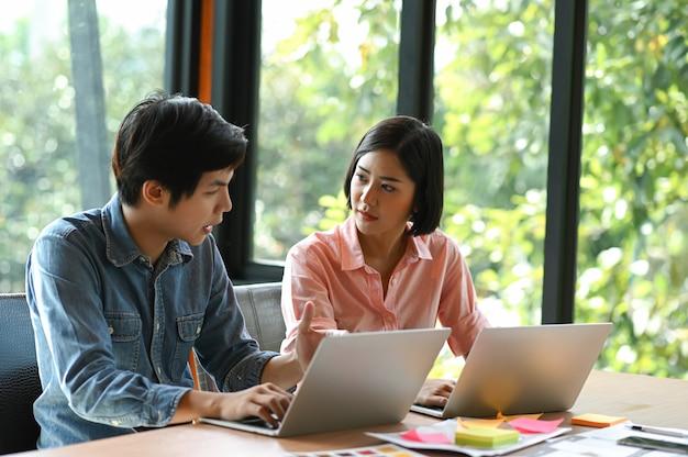Nieuwe generatie jonge mannen en vrouwen zitten, raadplegen, werken en gebruiken laptop op een bureau.