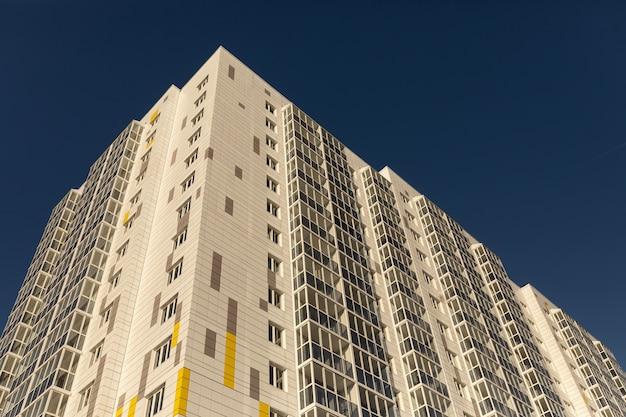 Nieuwe gevel met meerdere verdiepingen, ramen en flatgebouw. fragment van een nieuw elite woongebouw of commercieel complex tegen een blauwe hemel. hoek perspectief.