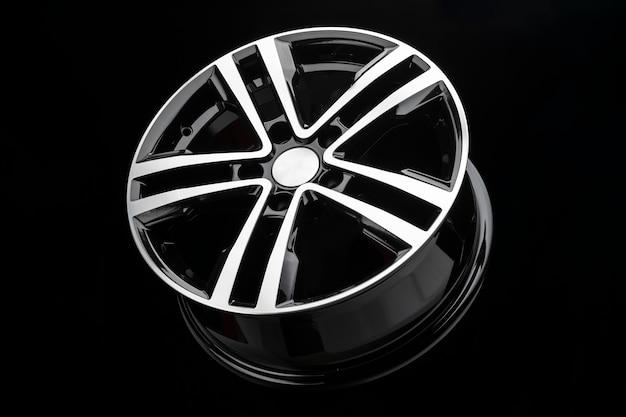 Nieuwe glanzende lichtmetalen velg, kleur zwart met zilverkleurig front. donkere achtergrond, zijaanzicht.