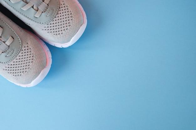 Nieuwe grijze sneakers op pastel blauwe achtergrond