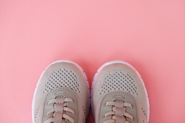 Nieuwe grijze sneakers op pastel roze achtergrond