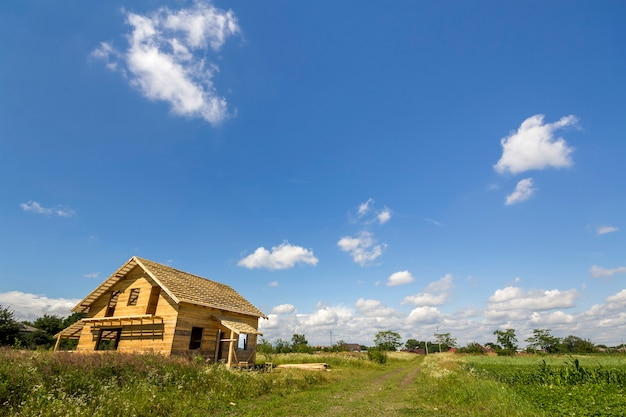 Nieuwe houten ecologische niet afgewerkt huisje van natuurlijke materialen in aanbouw in groene veld op verre dorp en blauwe hemel kopie ruimte achtergrond. oude tradities en modern bouwconcept.