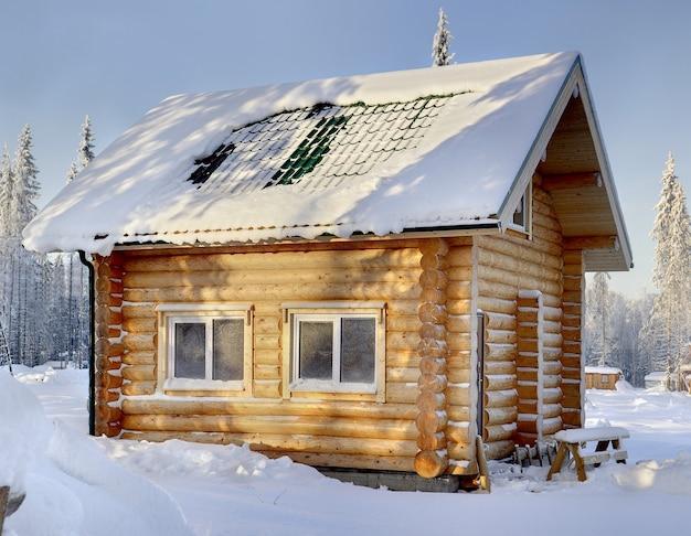 Nieuwe houten russische sauna op zonnige winterdag, van buitenaf, tegen de achtergrond van besneeuwd bos.