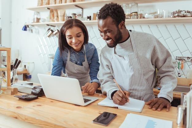 Nieuwe ideeën. aangename jonge barista's die op internet surfen op zoek naar ideeën voor hun nieuwe koffiehuis terwijl ze bezig zijn met het creëren ervan