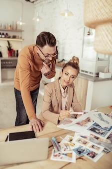 Nieuwe ideeën. gerichte modeontwerper en zijn glimlachende assistent werken aan het maken van nieuwe kleding.