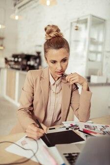 Nieuwe ideeën introduceren. geconcentreerde modeontwerper die aan tafel zit en het concept van haar nieuwe collectie heroverweegt terwijl ze schetsen maakt.