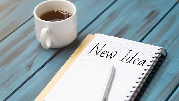 Nieuwe ideetekst op kladblok met kantooraccessoires.