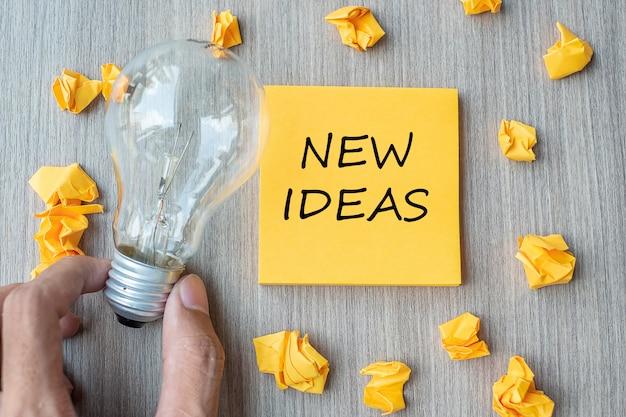 Nieuwe ideewoorden op gele nota en afgebrokkeld document met zakenman