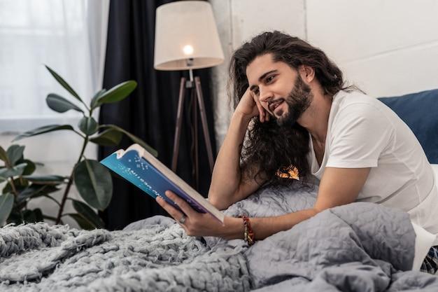 Nieuwe informatie. positieve aardige man die lacht terwijl hij zich concentreert op het lezen van een boek