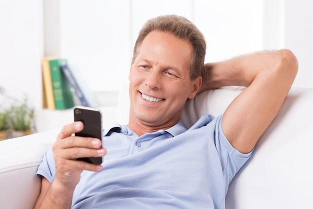 Nieuwe inkomende berichten lezen. vrolijke volwassen man die mobiele telefoon vasthoudt en ernaar kijkt terwijl hij thuis op de bank zit
