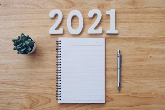Nieuwe jaar 2021 lijst. bureau tafel met notebooks en pancil met potplant.