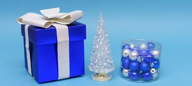 Nieuwe jaar samenstelling kunstmatige kerstboom cadeau en decoraties op blauwe achtergrond kerst wi...