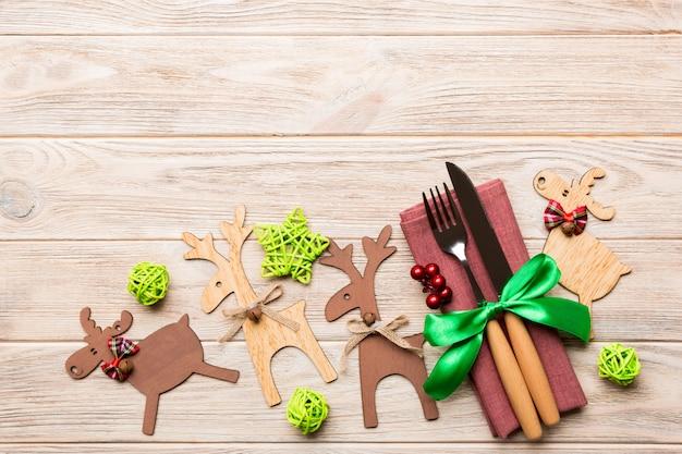 Nieuwe jaarreeks van vork en mes op servet, hoogste mening van kerstmisdecoratie en rendier op het dinerconcept van de houten, vakantiefamilie
