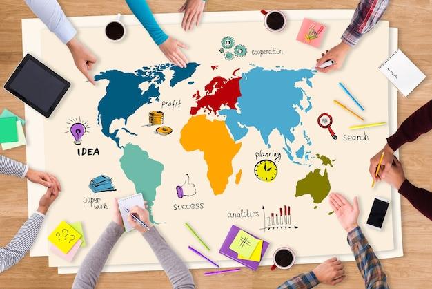 Nieuwe kansen bespreken. bovenaanzicht van papier met kleurrijke schetsen op de houten tafel en mensen die eromheen zitten