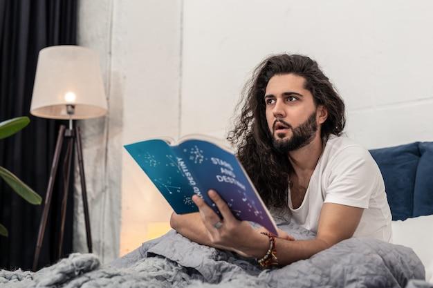 Nieuwe kennis. aardige attente man die onder de indruk is terwijl hij nieuwe nuttige informatie uit het boek leert