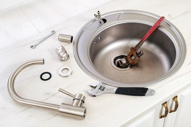 Nieuwe kraan en gereedschap voor installatie in de gootsteen