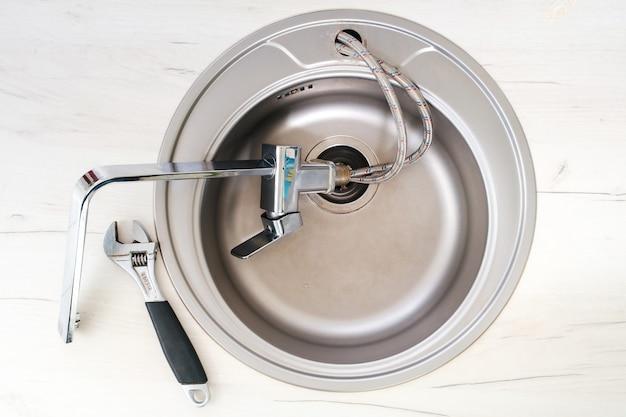 Nieuwe kraan en verstelbare sleutel voor installatie in de gootsteen