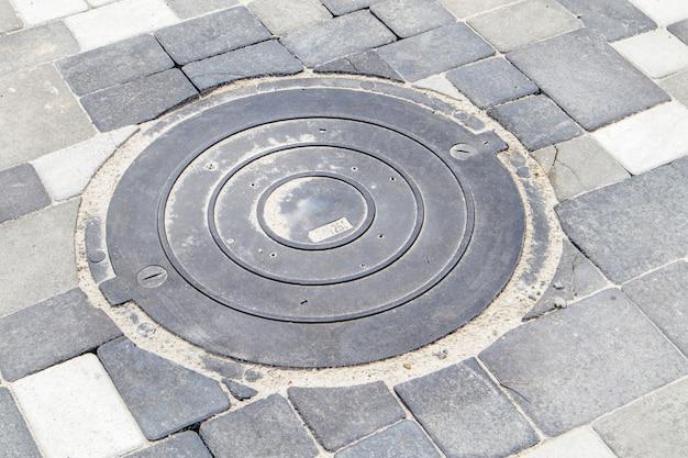 Nieuwe kunststof putdeksel op het trottoir bekleed met grijze bestrating platen. het concept van riolering, ondergrondse communicatie. het plaatsen van een nieuw rioolluik. bouwindustrie.