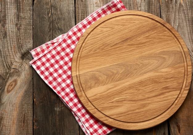 Nieuwe lege ronde houten snijplank op grijze tafel