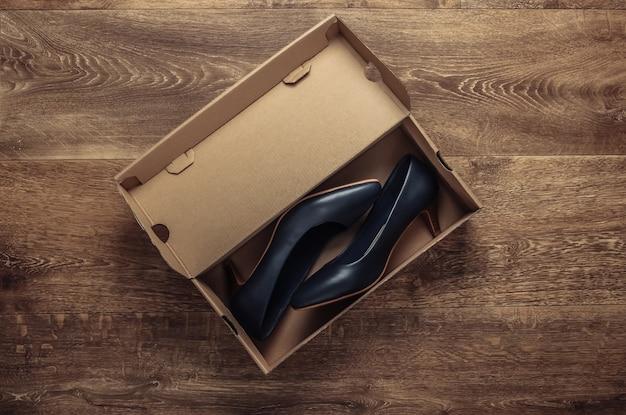Nieuwe leren hakken met een kartonnen doos op de grond. bovenaanzicht